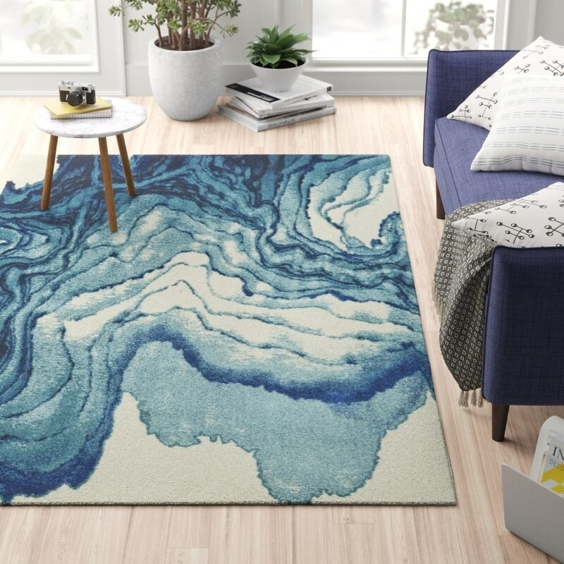 """The rug in blue, which a white base and abstract """"waves"""" of marbled blue"""