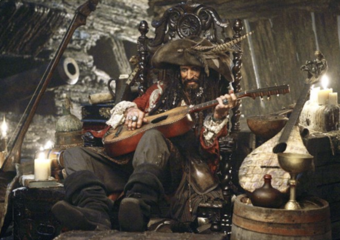 Keith Richards dressed as a pirate strums a guitar
