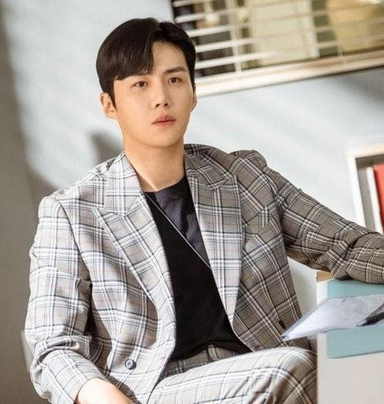 A close up of Han Ji-pyeong; he is wearing a tweed suit with a black t-shirt