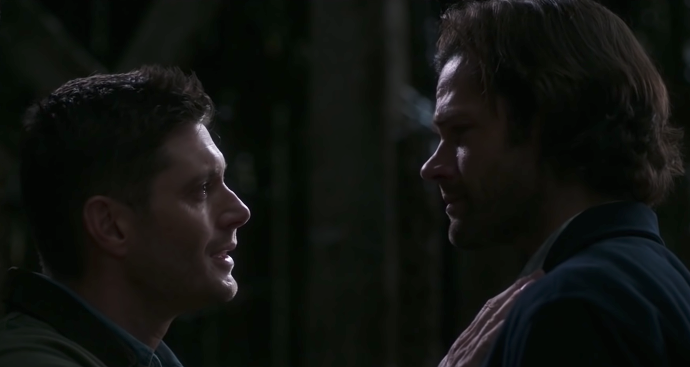 A closeup of Dean tearfully talking to Sam