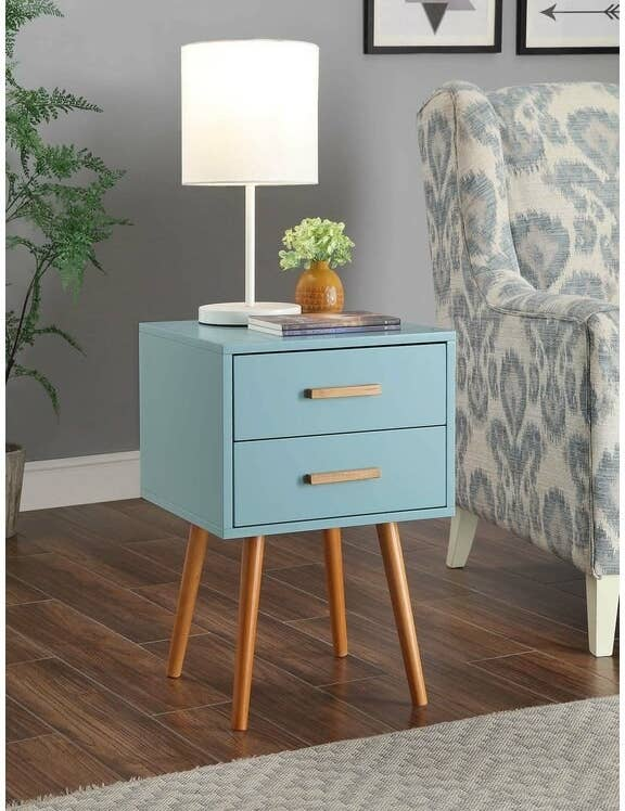 The table in blue, with thin natural-tone wood legs, and two narrow drawers with oblong handles