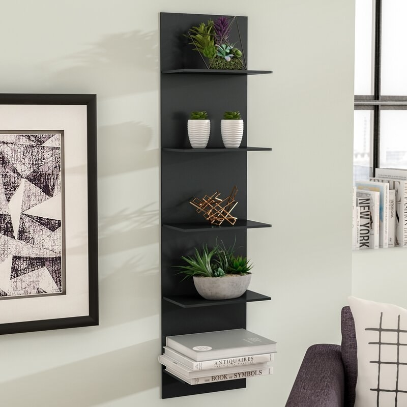 The shelving unit, which is flat and mounted directly on the wall, with five simple, flat horizontal shelves extending from it