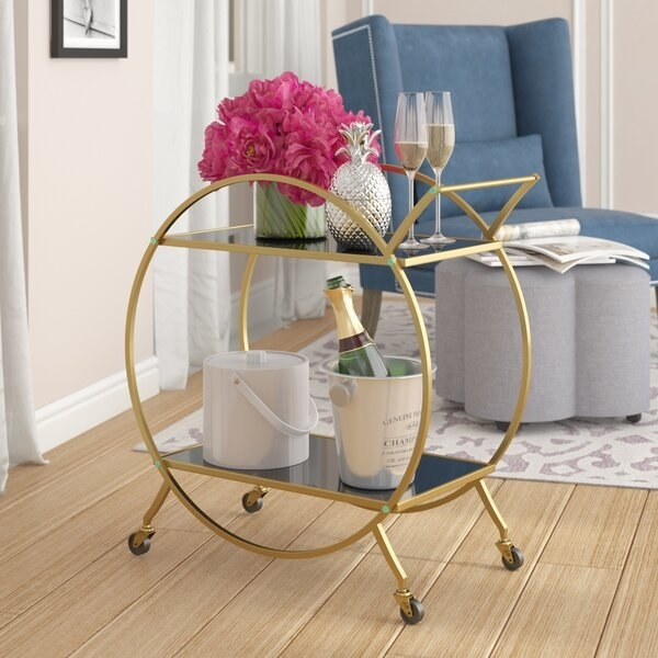 The bar cart, which has a circular gold-toned frame, two mirrored levels, a handle, and four wheels
