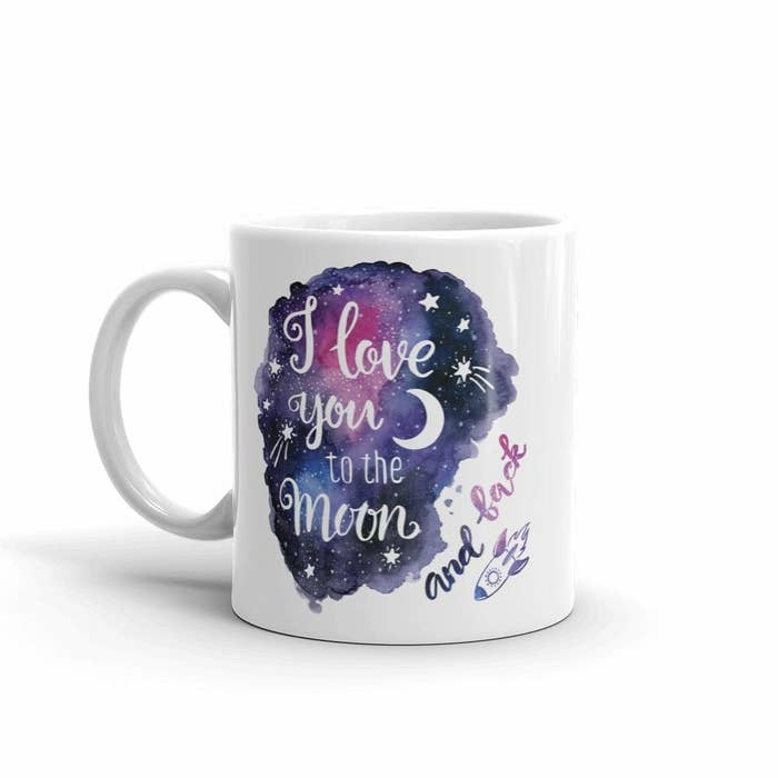 """A white mug that has a galaxy design and a rocket doodle. It says, """"I love you to the moon and back""""."""
