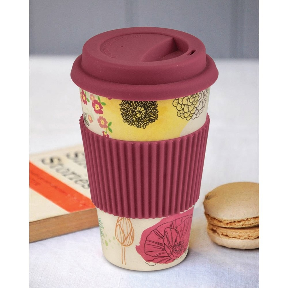 A travel mug with a pink and yellow floral design on it, a dark pink silicone mug glove and a sipper top.