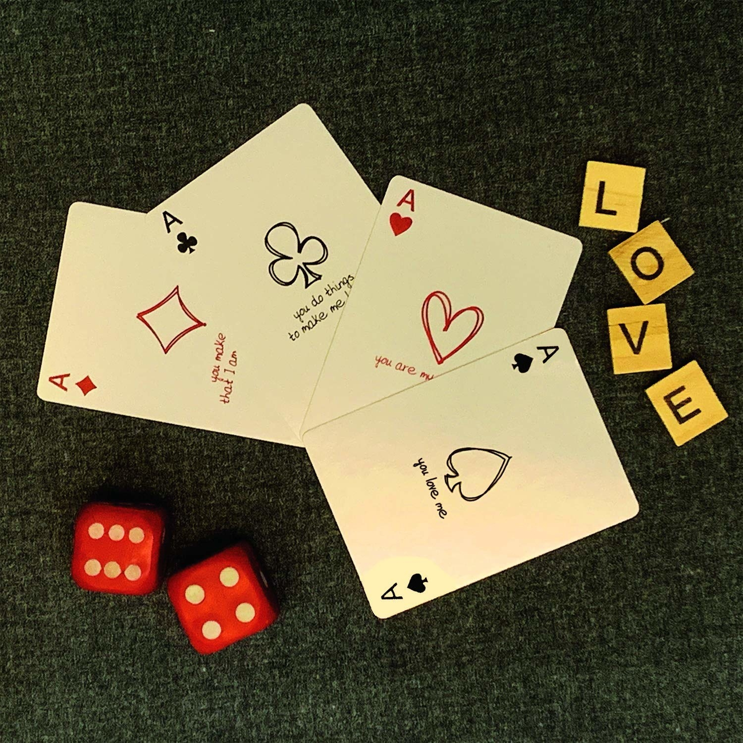 The cards pictured with 2 red dice and scrabble tiles that spell out the word 'love'.