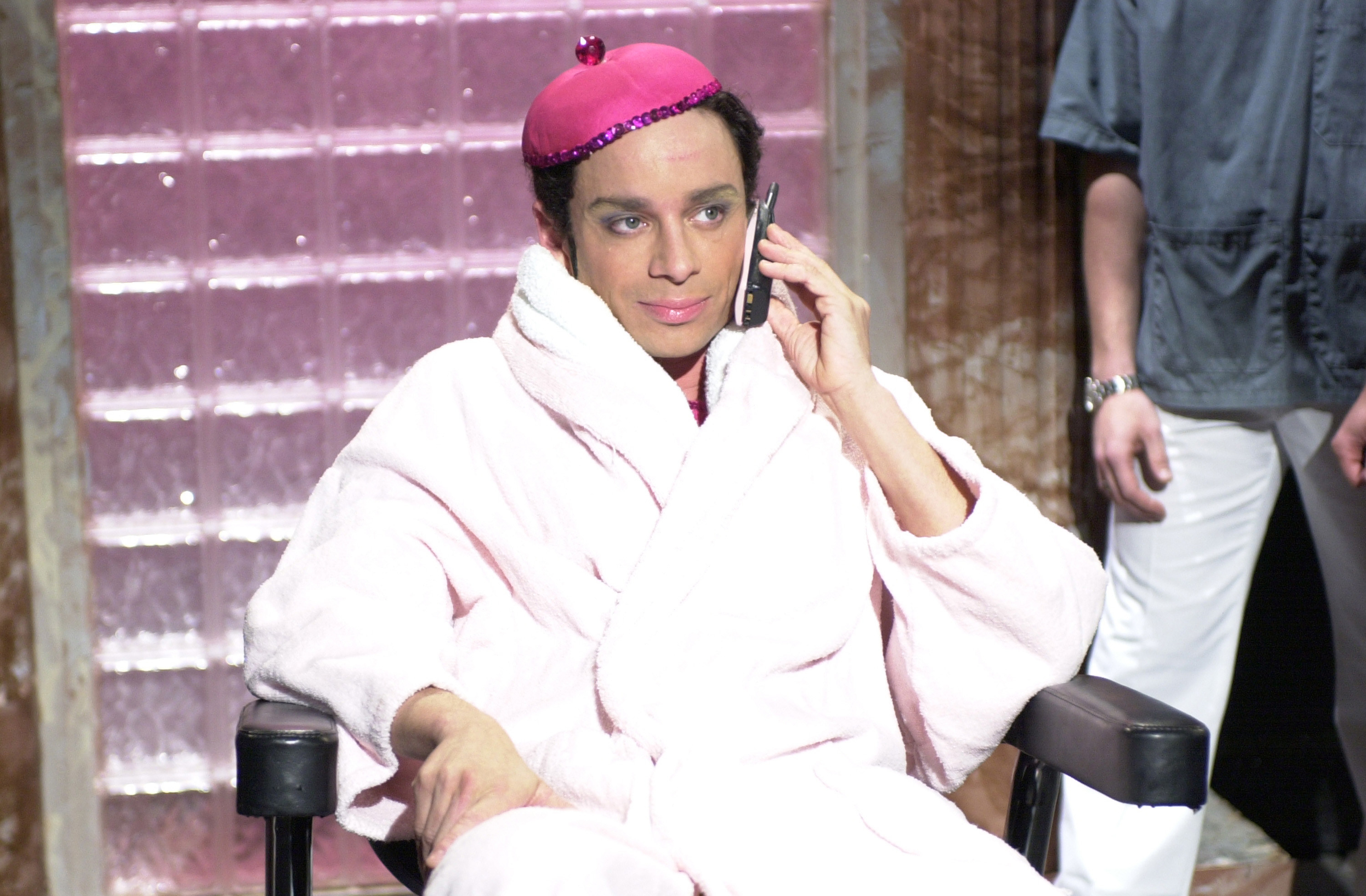 Chris Kattan as Mango in a robe sitting in a chair while talking on a cell phone