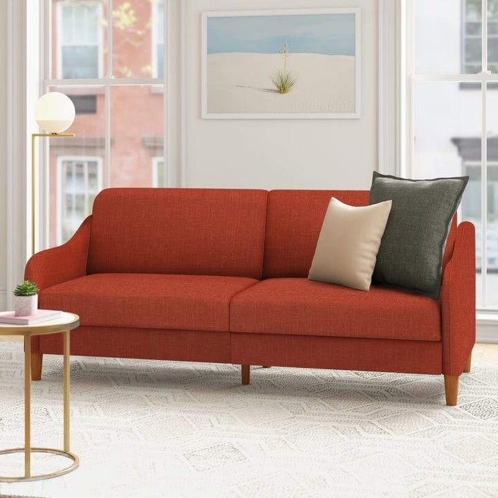 The couch in red, in the upright position, with two large cushions