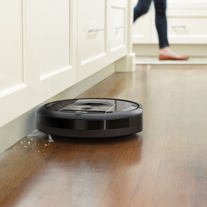 The Roomba, which is round and small, cleans using vacuum suction and small brooms