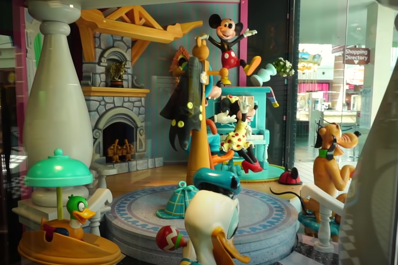 A Mickey, Goofy, Minnie, and Pluto statue waving to people in a living room window display