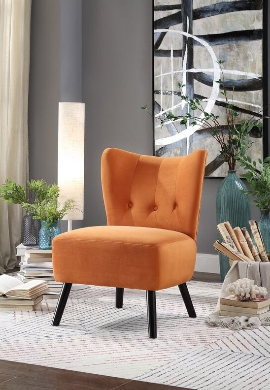 The chair in orange, which has black splayed wooden legs, no arms, and a button-tufted back