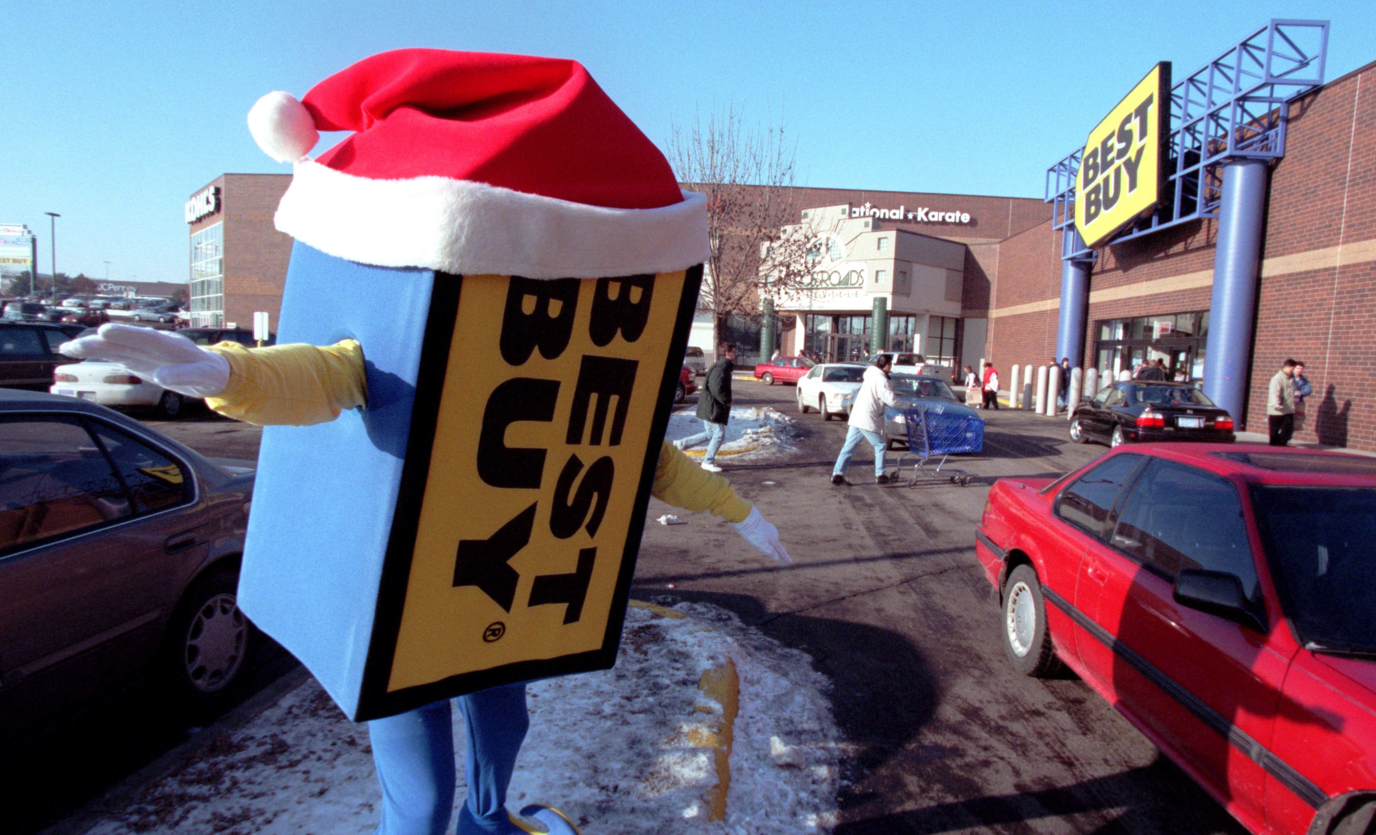 The Best Buy mascot dancing in a parking lot with a Santa hat on
