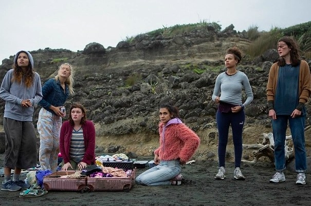 The cast of The Wilds stand on a beach around open suitcases