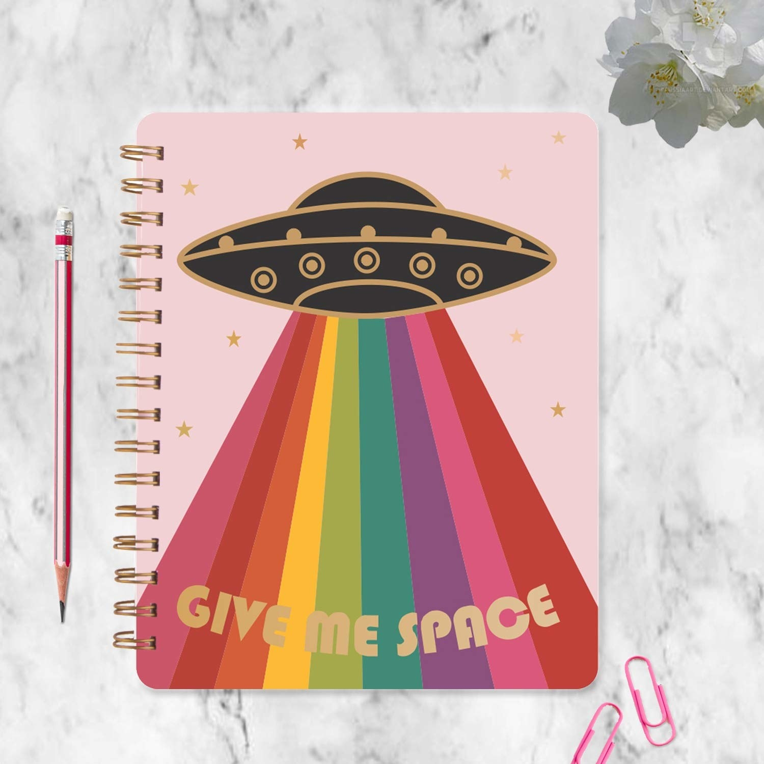 A pink, spiral-bound journal with a black UFO beaming down rainbow colours and the text 'Give Me Space' in golden over the beam.