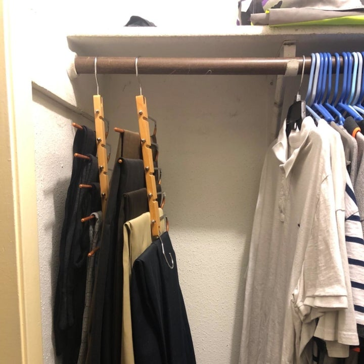 reviewer photo showing how the hanger collapses to take up a fraction of the space while still holding 5 pairs of pants