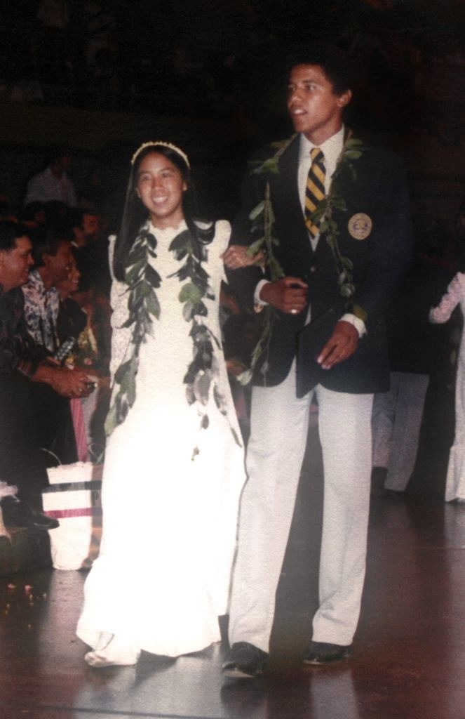 Barack Obama graduating from high school in Hawaii, walking down an aisle with a female classmate