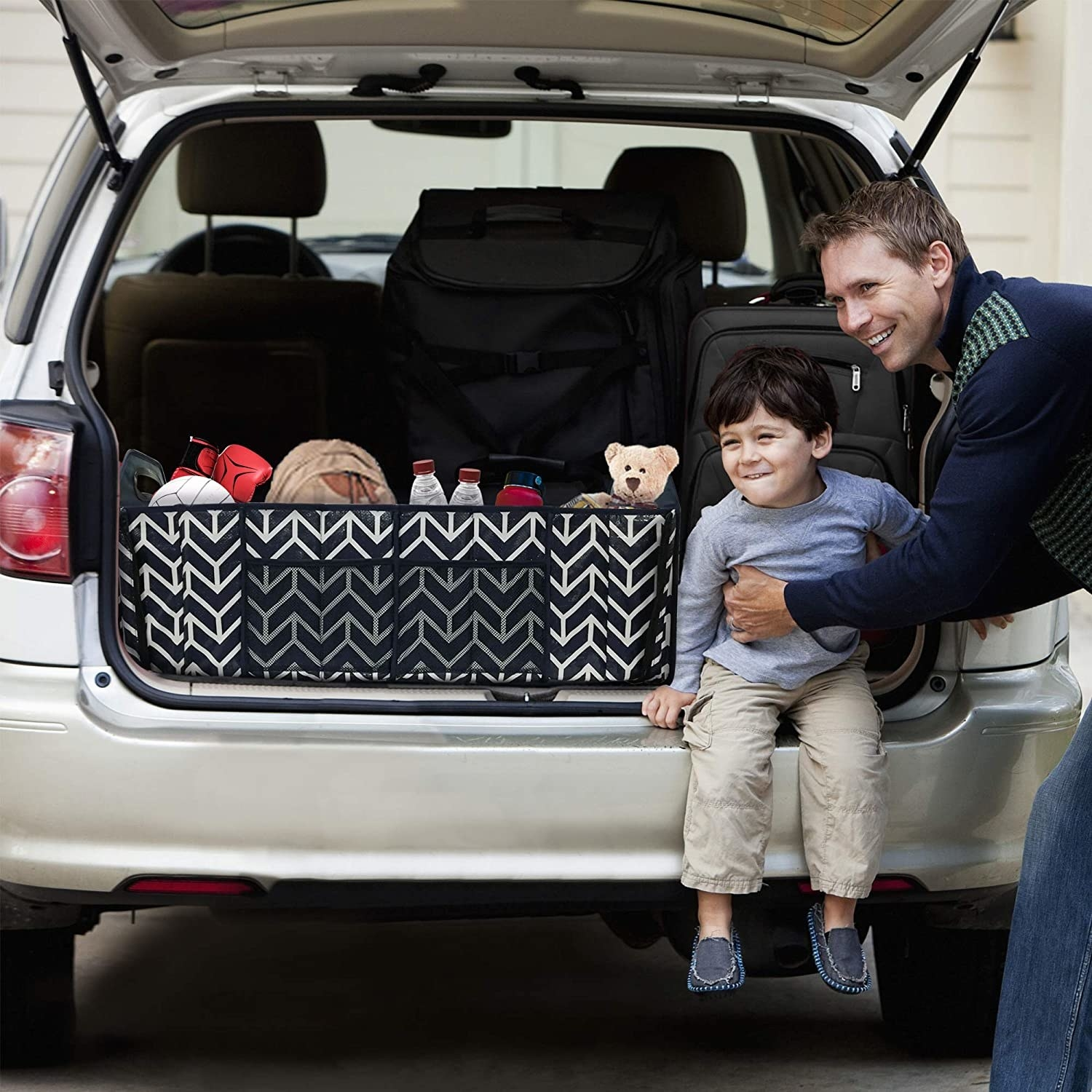 person holding child sitting on trunk with the trunk organizer