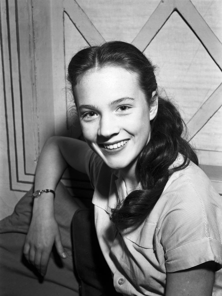 16-year-old Julie Andrews posing happily for a picture with long, brown hair and her arm leaning on the couch