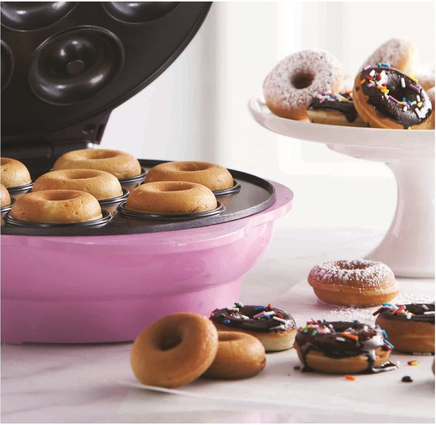 A close up of the open donut maker containing freshly baked donuts