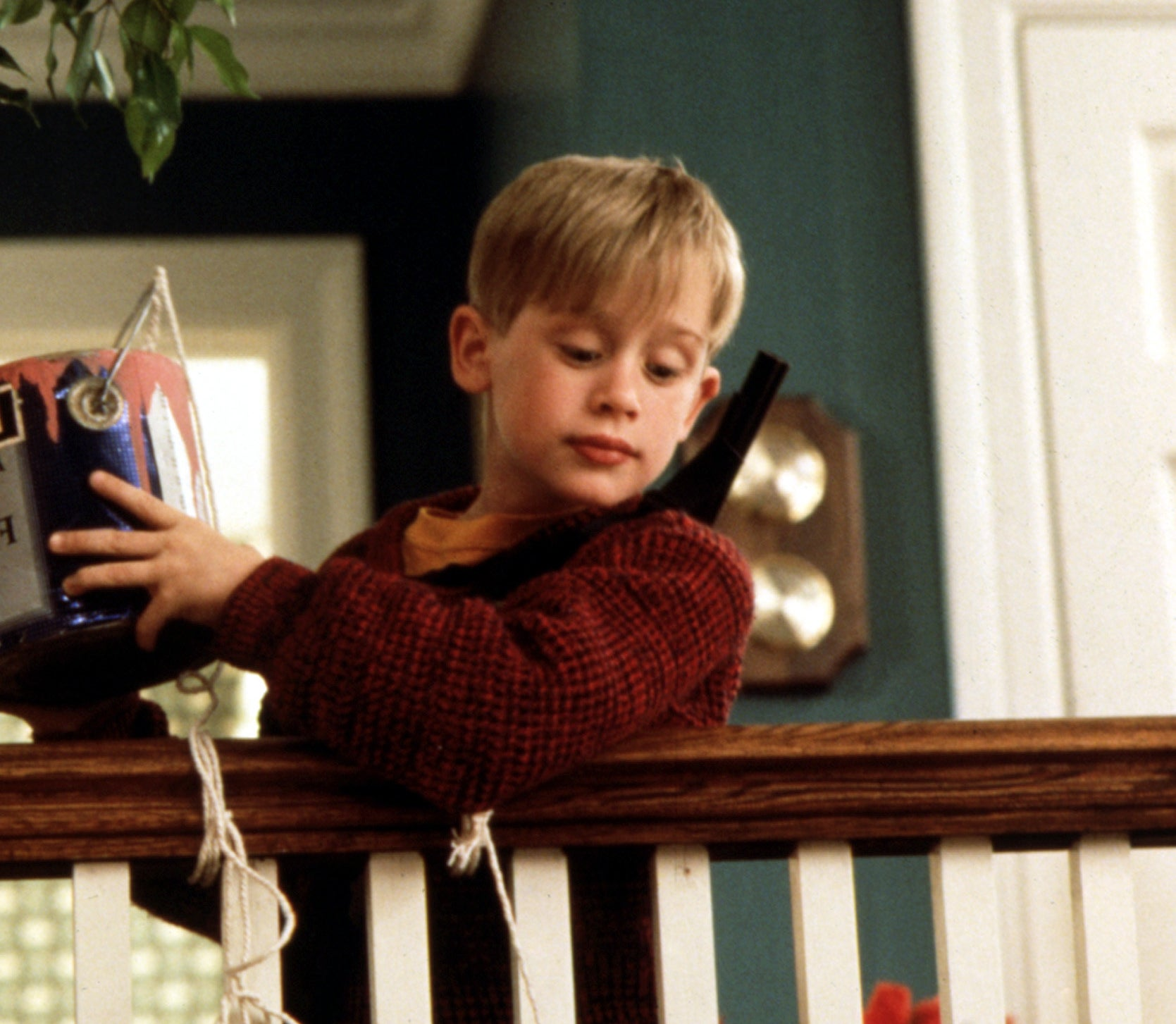 Macaulay Culkin as Kevin McCallister ready to dump a can of paint on his victims