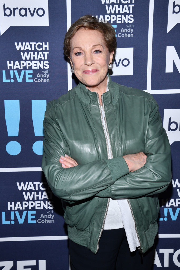 """Julie Andrews crossing her arms and posing for a picture while wearing a leather jacket on the red carpet for """"Watch What Happens Live! with Andy Cohen"""" in 2019"""