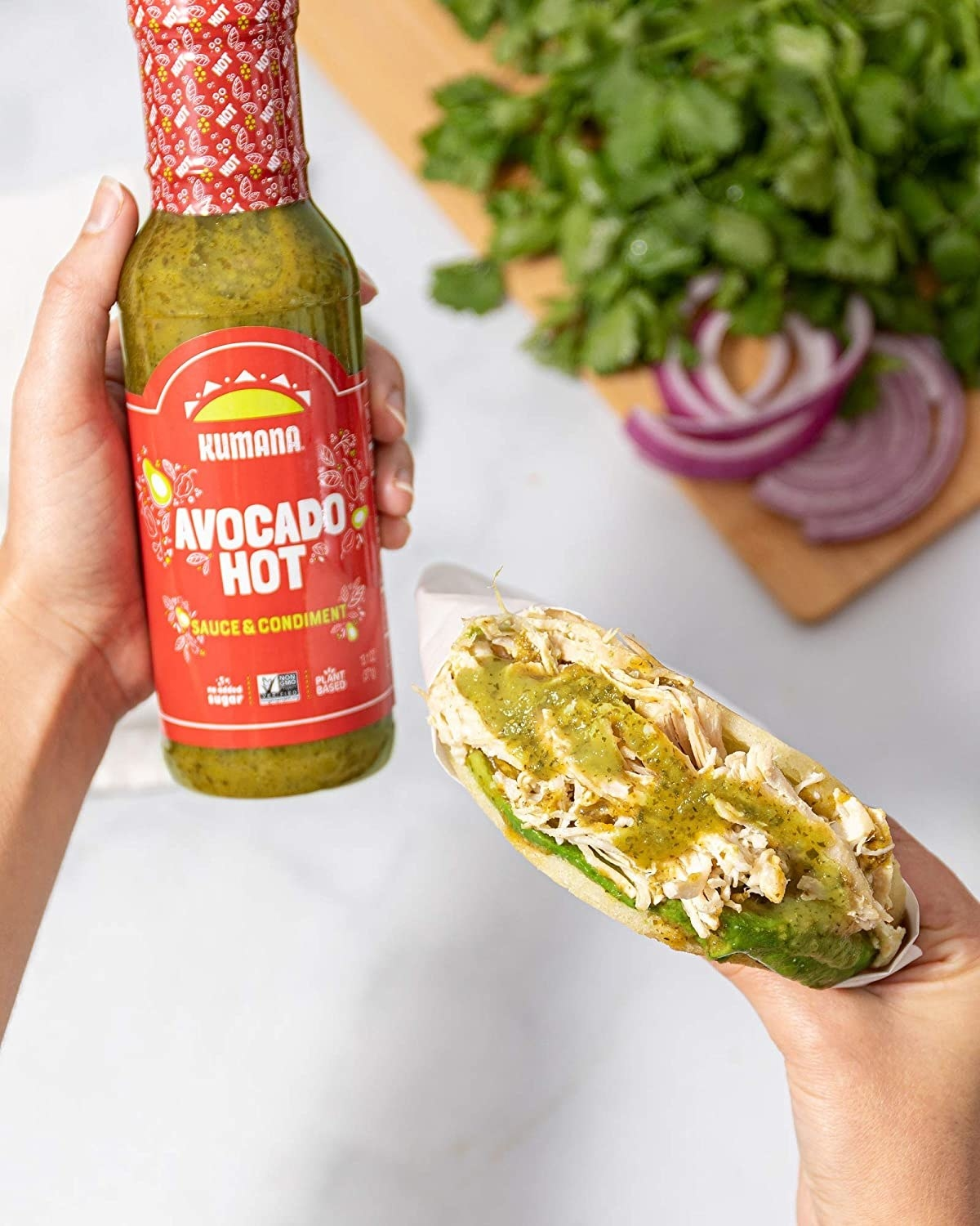 Avocado hot sauce bottle and a pita with sauce in it