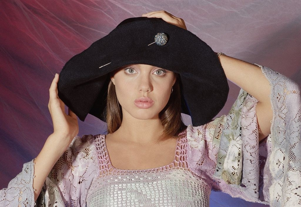 Angelina Jolie posing for a portrait in 1991 wearing an oversized hat and a floral shawl