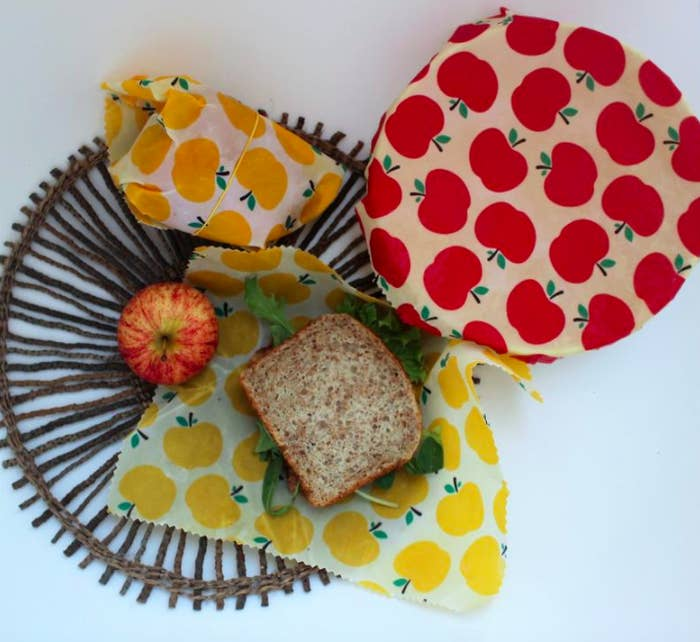 A trio of beeswax wraps next to bread and a fresh apple