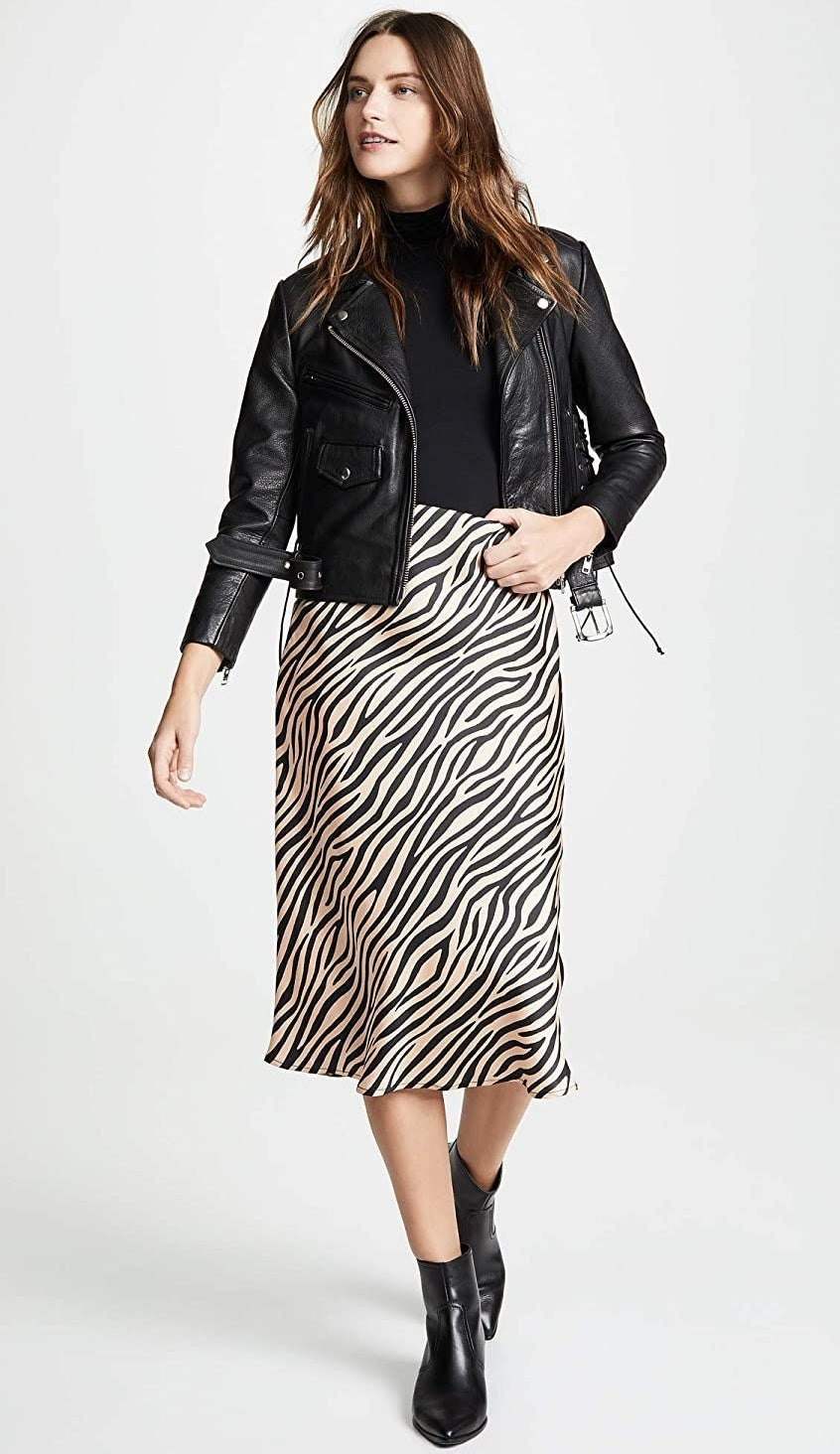 A model wearing the black and tan below-the-knee skirt with a moto jacket
