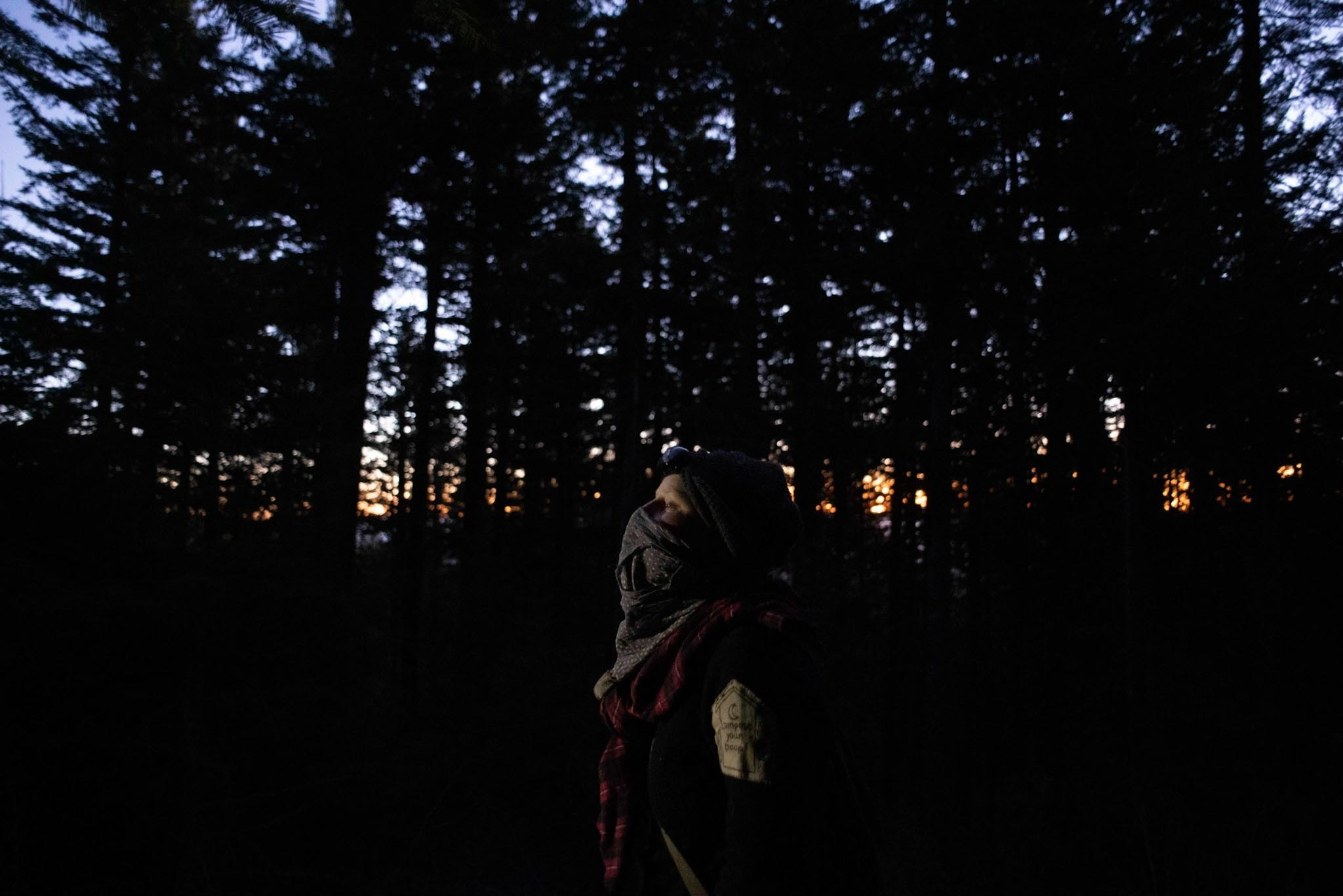 An activist wearing a bandana in the woods at sunset