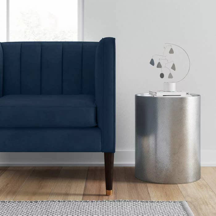 The round silver table next to a couch