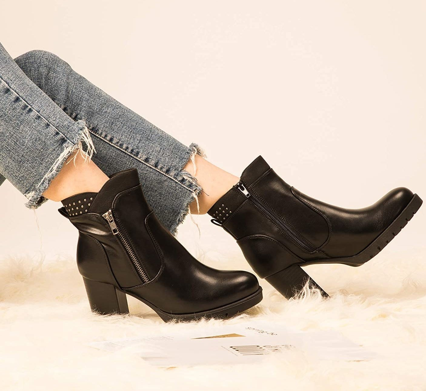 Model wearing the black high heeled booties with a silver zipper and stud details at the back of the ankle