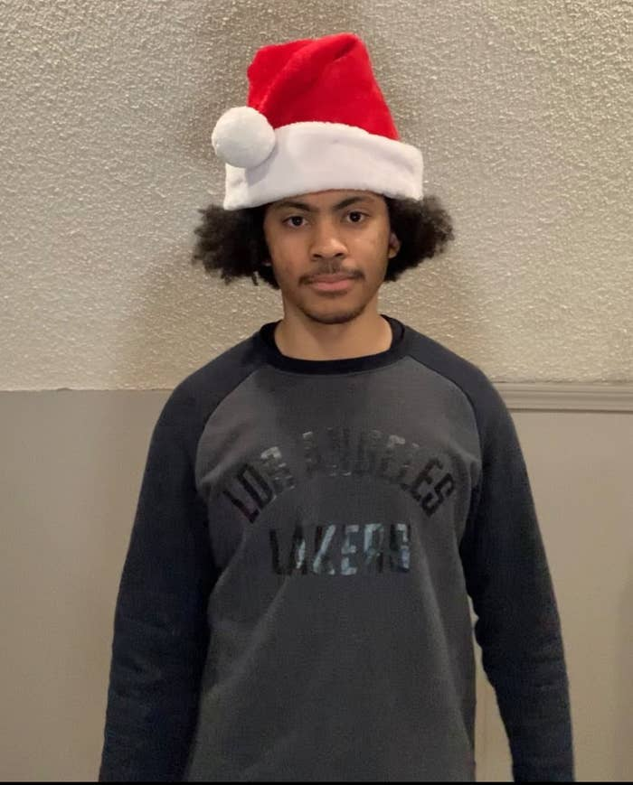 A man, not smiling, stands against a wall, wearing a Santa hat and a Los Angeles Lakers T-shirt