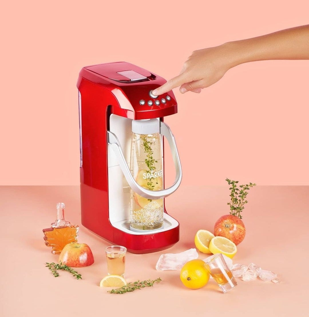 A person pressing the top button on the sparkling water maker, surrounded by apples, maple syrup, herbs, and lemons