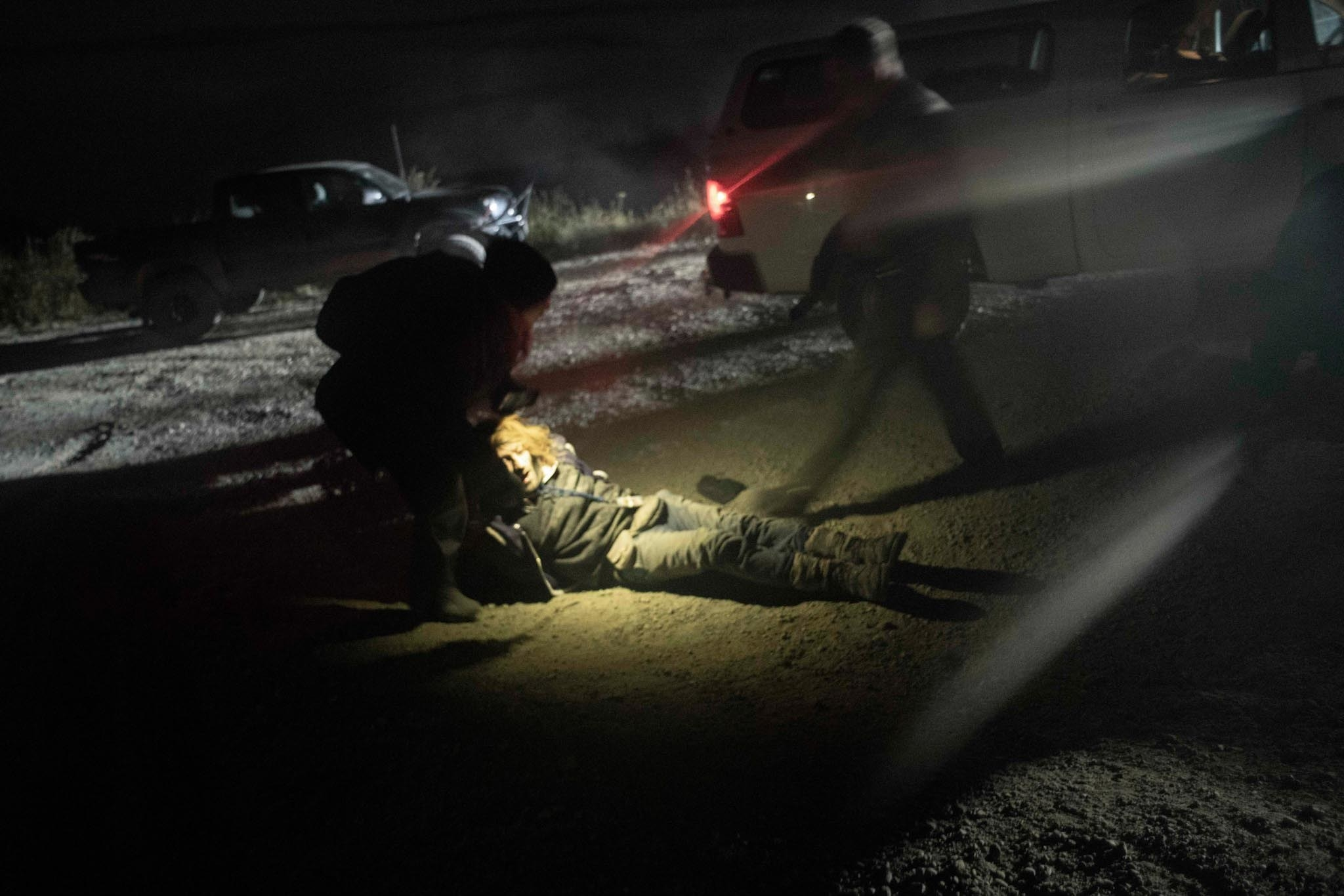 An activist is dragged on the ground by another activist as the cops approach