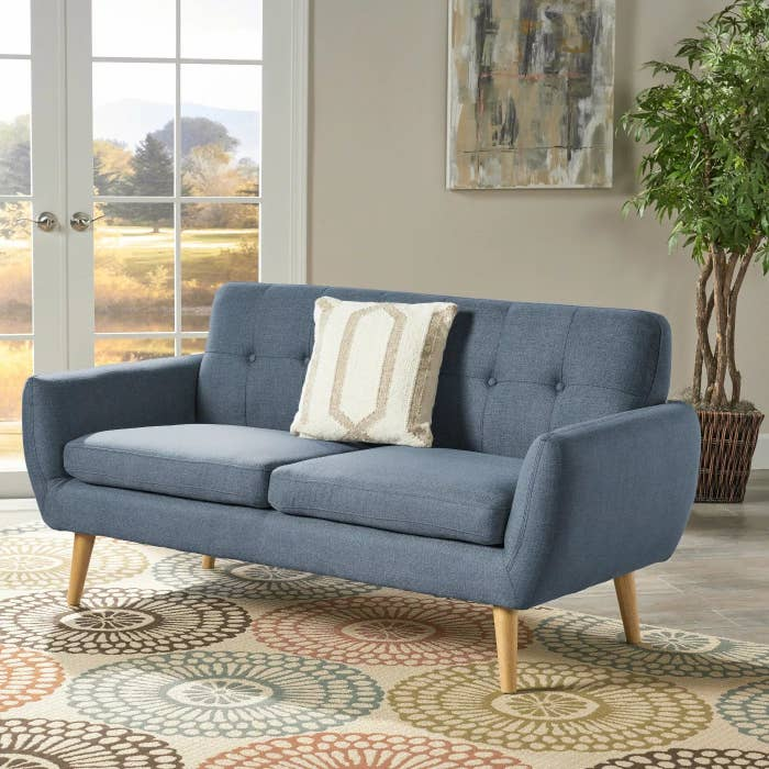 The blue sofa with wooden legs