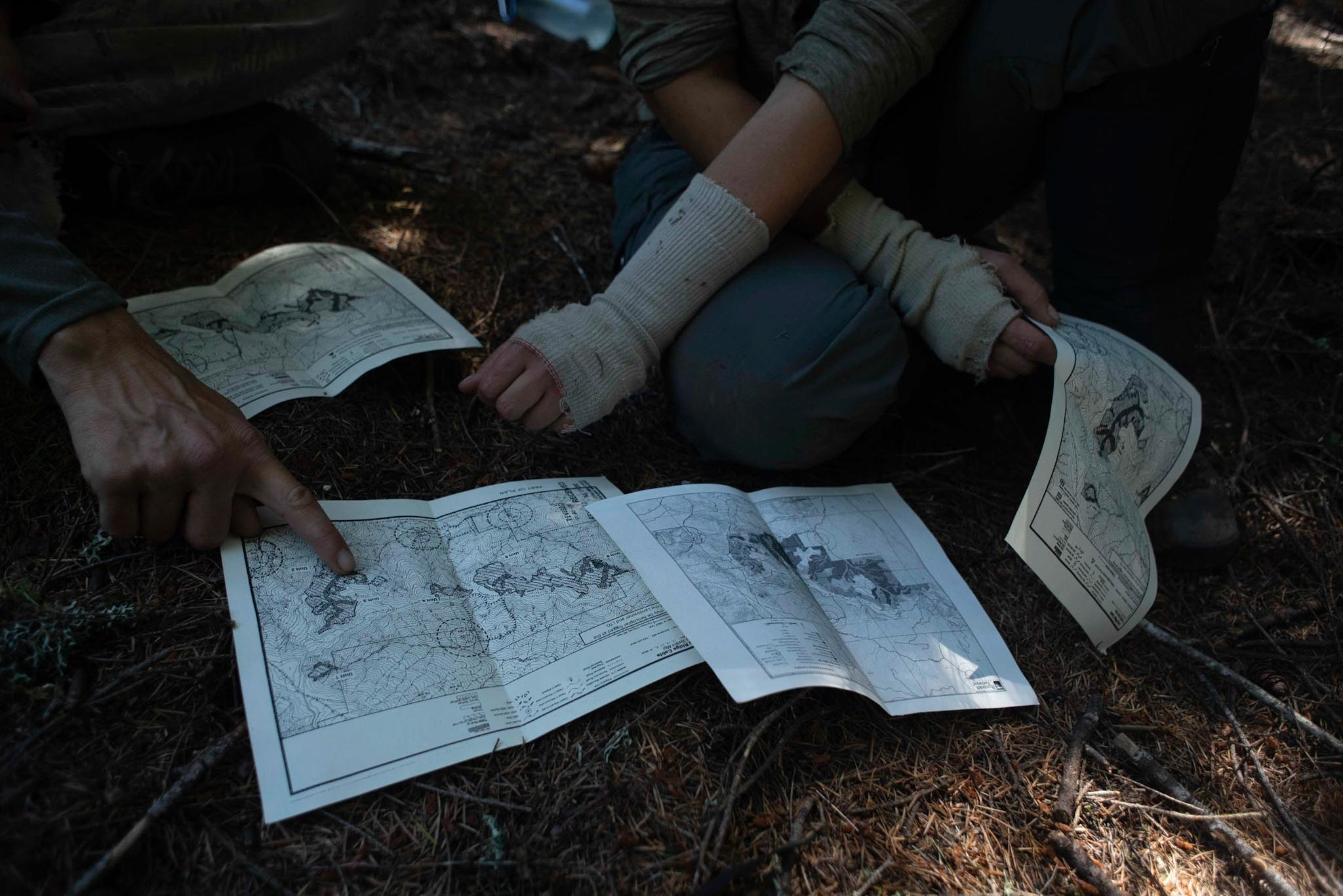 Two people study maps while sitting on the forest floor