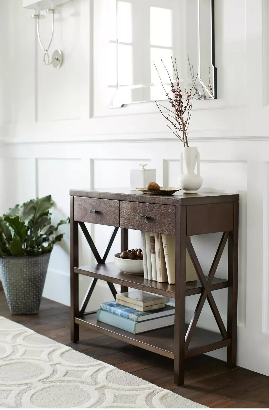 The brown console table with two shelves and two drawers in an entryway