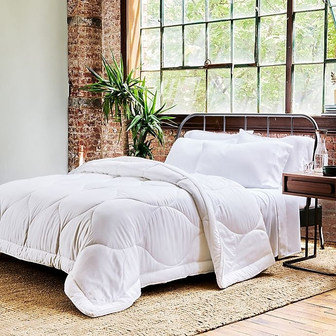 the buffy cloud down alternative comforter on a bed