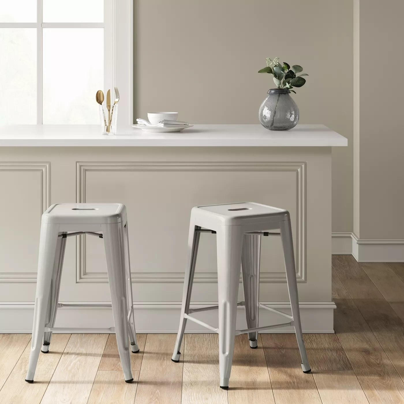 The gray bar stools underneath a kitchen counter