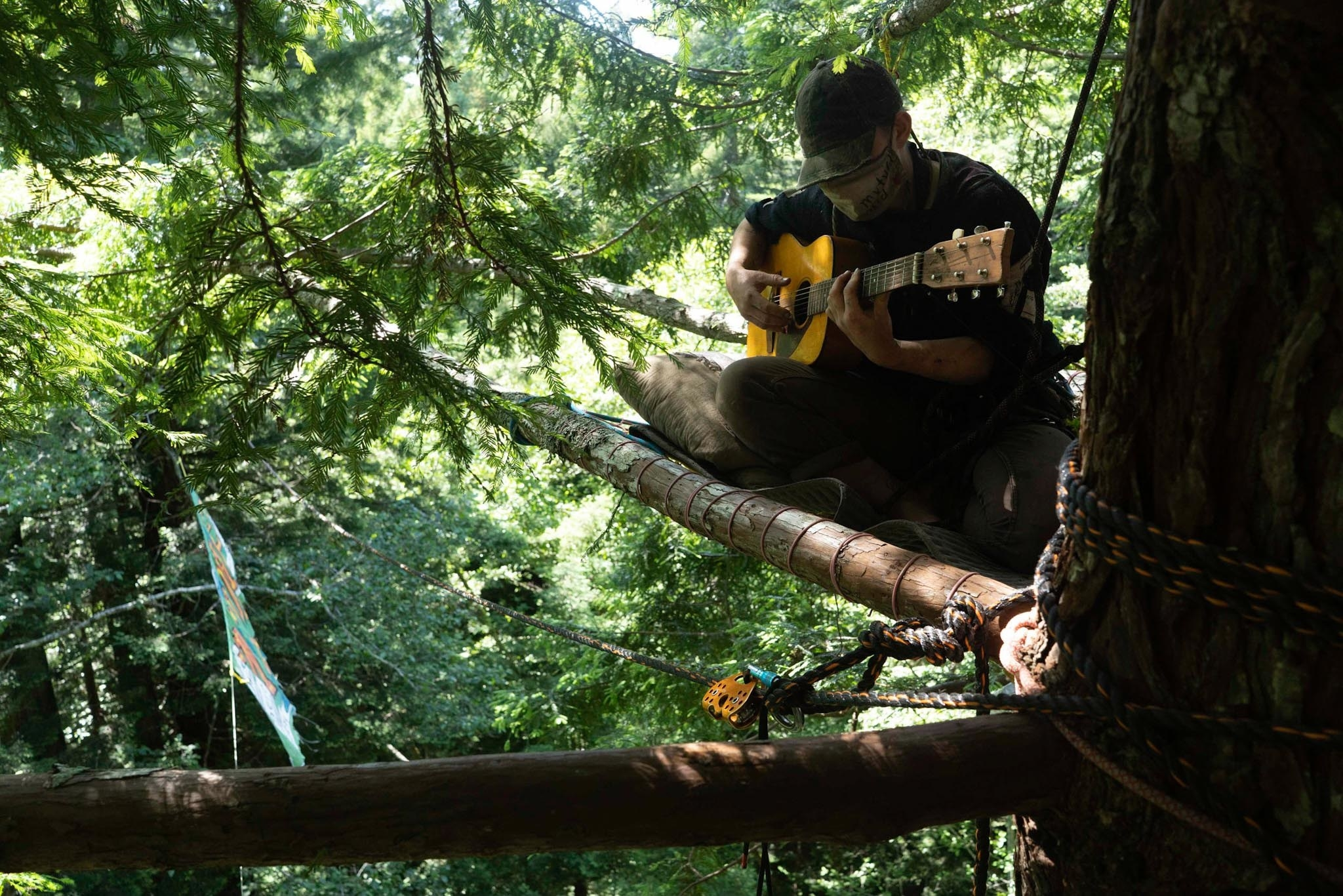 A person wearing a mask and a hat playing guitar on a platform in a tree