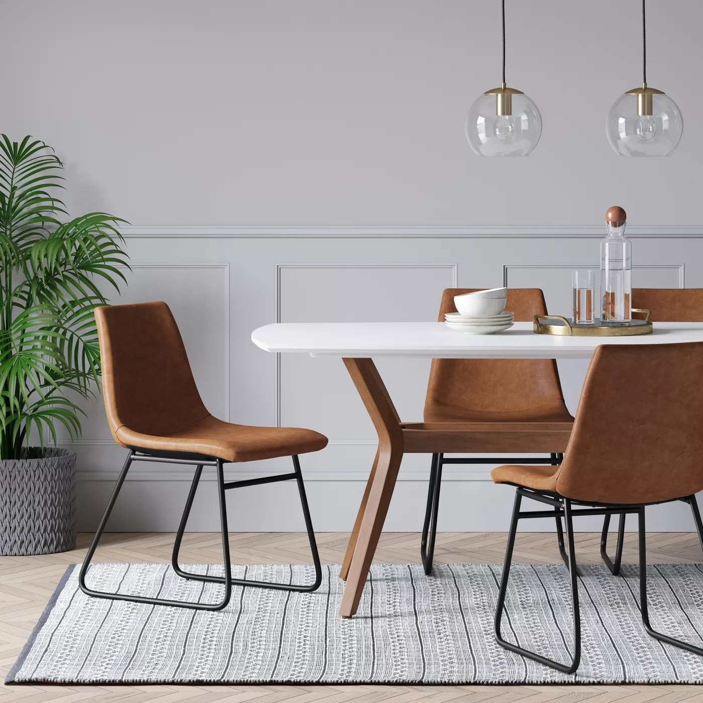 The brown chairs with black legs around a dining table