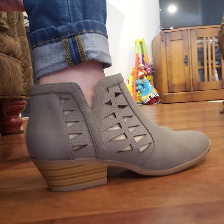 A reviewer wearing the booties in gray