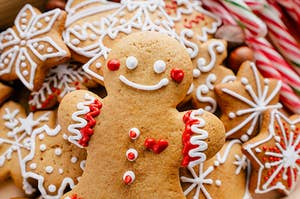 A smiling gingerbread man laying on top of a pile of gingerbread snowflakes