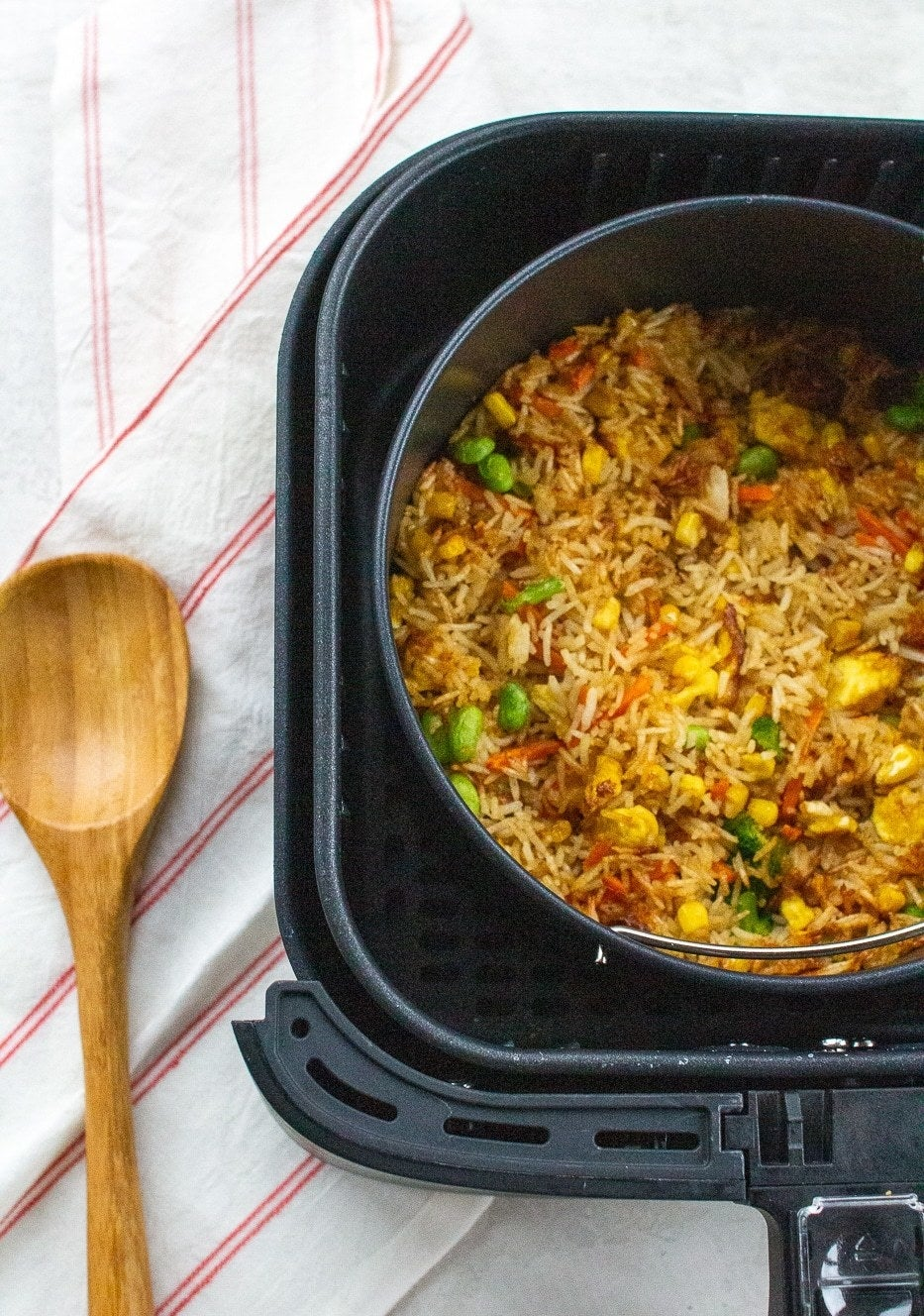 Fried rice cooking in a baking dish in the basket of an air fryer.