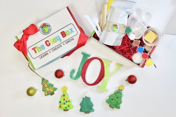 christmas themed clay project with mini christmas trees, letters that spell joy, paint, brushes, and more