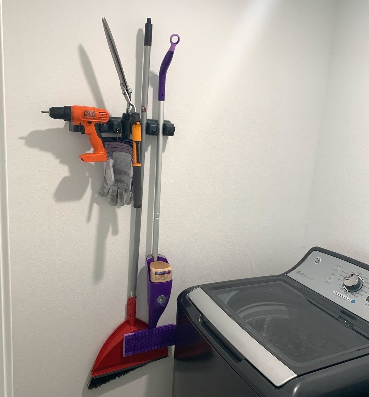 reviewer photo showing the organizer with a broom, Swiffer, and even a drill attached to it