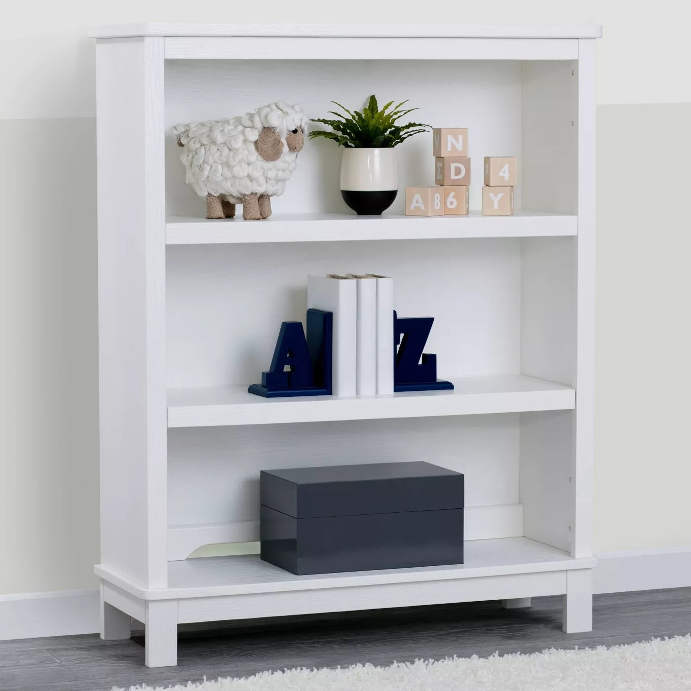 The white bookcase with three shelves in a nursery