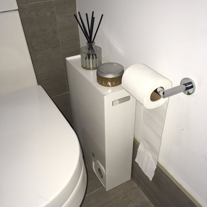 reviewer photo showing toilet paper stocker in their bathroom with a candle on it