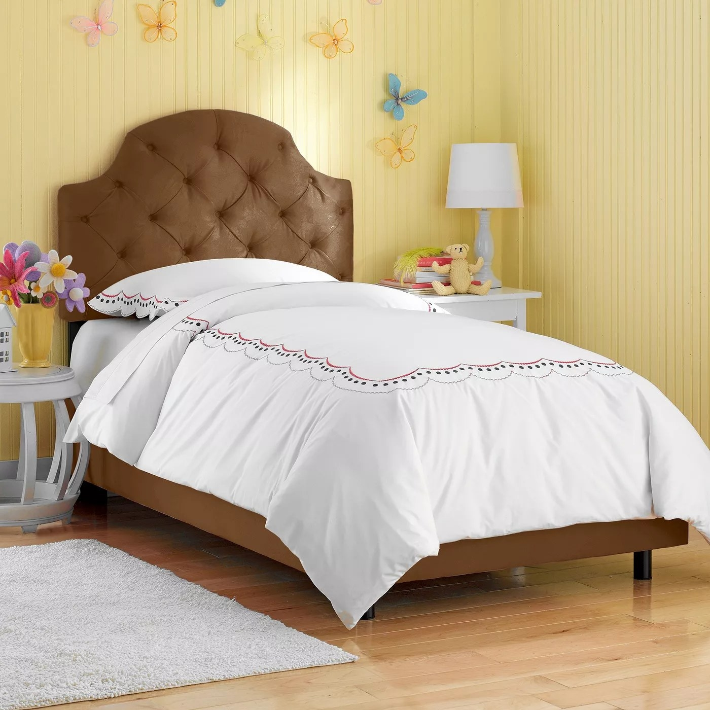 The brown bed with a tufted headboard